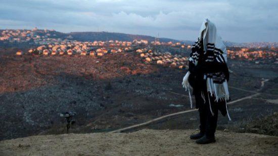 Tampak salah satu warga sedang menyaksikan deretan pemukiman di Tepi Barat yang menjadi wilayah sengketa (REUTERS/Baz Ratner)