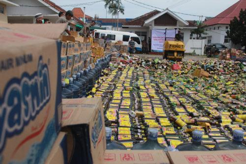 Sebuah alat berat sedang menggilas ribuan botol minuman di Bandarlampung,Senin (19/12). (Lampungnews/El Shinta)