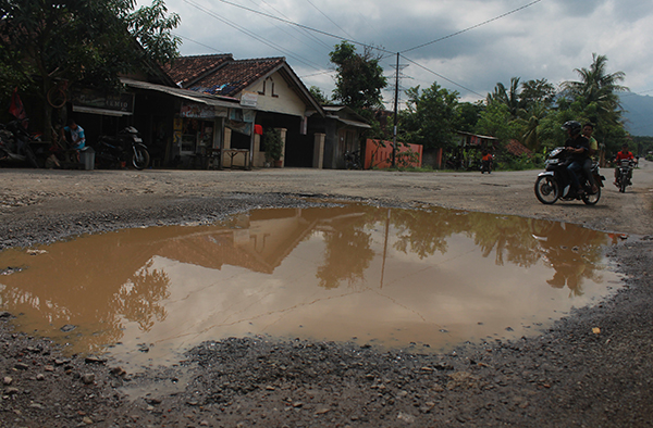 Kondisi jalan berlubang dan bergelombang menuju destinasi wisata Taman Boemi Kedaton dan Wira Garden di Jalan WA Rahman, Senin (2/1)