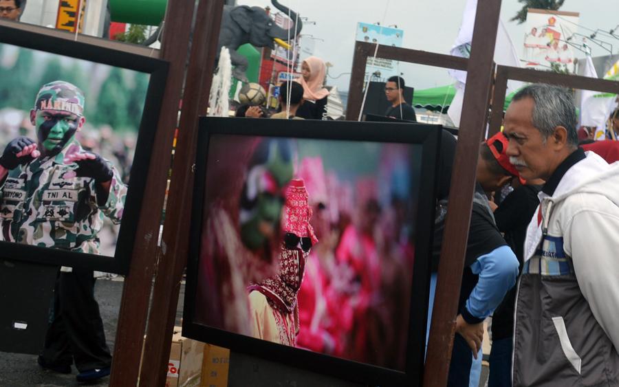 Masyarakat menyaksikan sejumlah foto karya jurnalis Lampung tergabung dalam Pewarta Foto Indonesia (PFI). (Lampungnews/Gatot Arifianto)