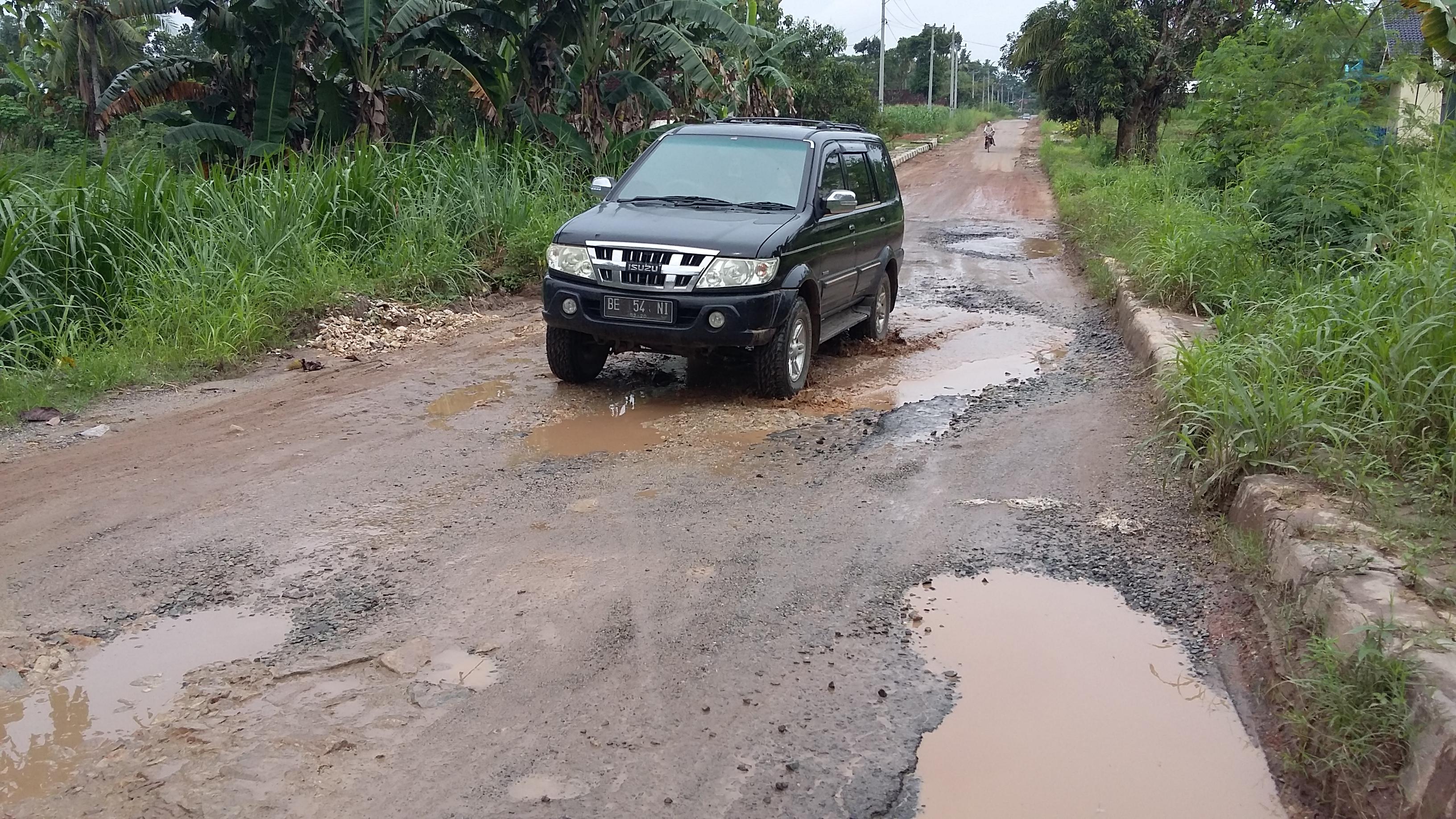 Mobil melintas di jalan Pondok Pesantren, Seputih Jaya, Gunung Sugih yang perlu diberbaiki. (Foto: lampungnews: Davit)