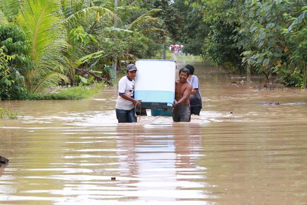 Warga mengevakuasi perabotan rumah tangga akibat banjir di Lampung Selatan. Foto: Lampungnews/Kristian Ali.