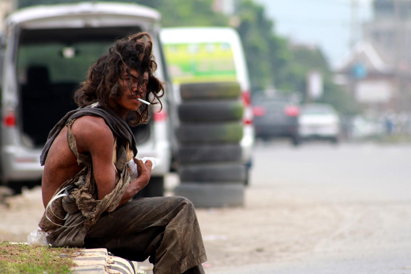 Orang gila yang merokok di Jalan Soekarno-Hatta, Tanjung Seneng. (Foto: Lampungnews/El Shinta).