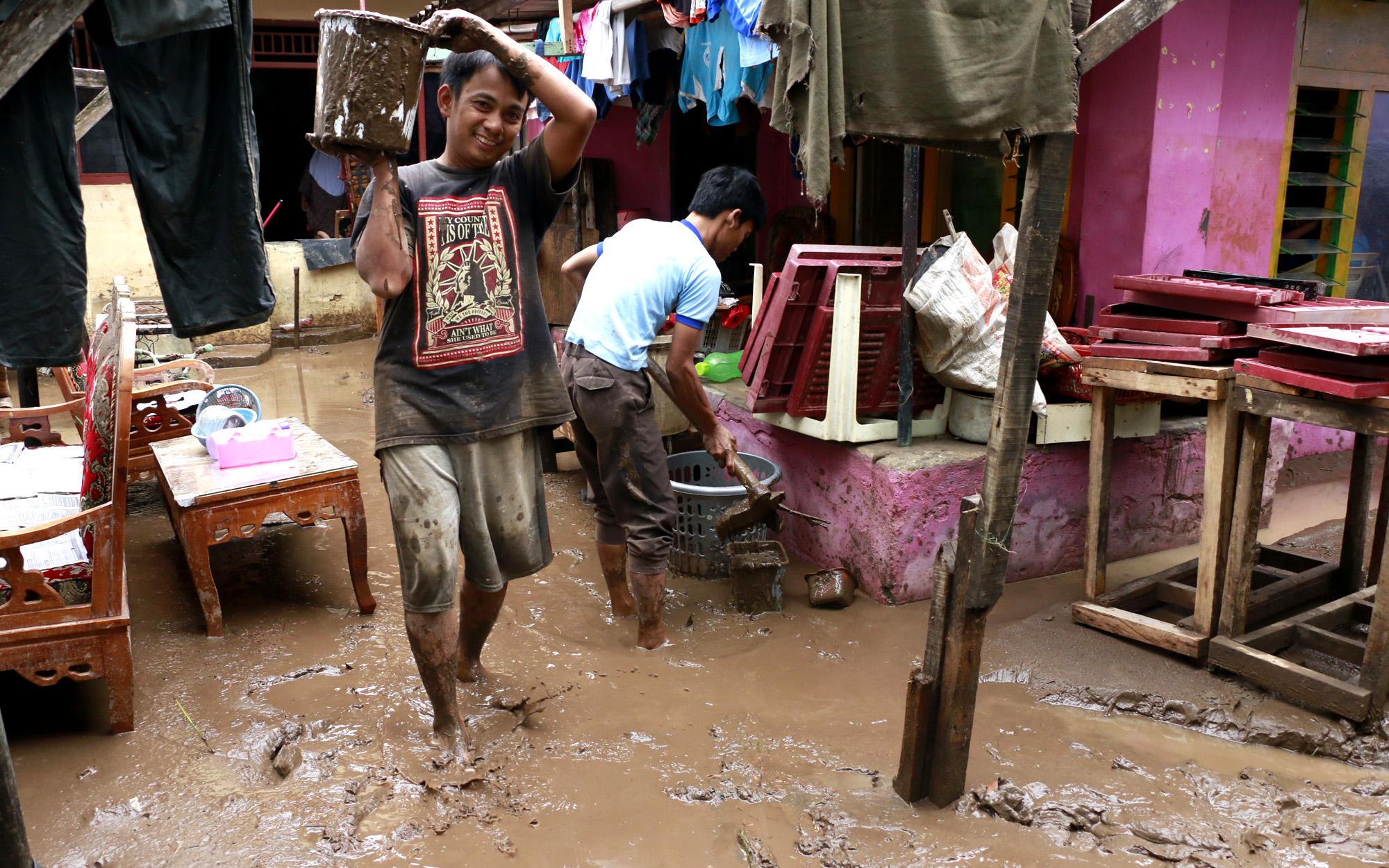 Sejumlah warga saling bahu membahu membersihkan lumpur sisa dari banjir setinggi dua meter yang merendam ratusan rumah warga di Telukbetung. (Lampungnews/El Shinta)