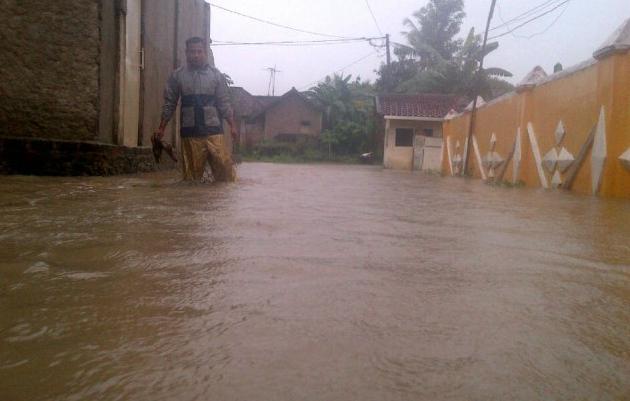 Agus (32), warga Kelurahan Pringsewu Selatan, Kecamatan Pringsewu melintasi lokasi tergenang air akibat hujan sejak Senin (20/2) malam. Anton/Lampungnews.com)