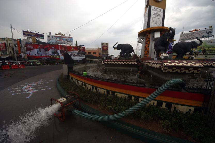 Personel Bagian Umum Pemerintah Kota Bandar Lampung membersihkan dan menguras kolam yang ada di Tugu Adipura, Senin (20/03). Pembersihan ini biasanya dikerjakan 12 orang setiap sebulan sekali. (Foto: Lampungnews.com/El Shinta)
