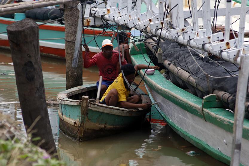 Dua orang nelayan Pulau Pasaran menggunakan perahu kecil untuk mengecat bagian bawah kapal bagan congkel. (Lampungnews/El Shinta)