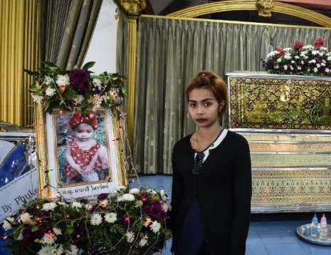 Jiranuch Trirat berdiri di depan peti mati berisi jenazah putrinya, Natalie, di sebuah kuil di Phuket, Thailand pada Kamis (27/4) [AFP/Lilian Suwanrumpha].