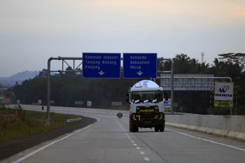Sebuah truk melintas di ruas pembangunan Tol Trans Sumatera (TTS) di Desa Sabah Balau, Lampung Selatan. Selain ruas jalan yang sudah dirigid, pada paket dua Sidomulyo-Kotabaru sejumlah rambu lalu lintas sudah mulai dipasang. (Lampungnews /El Shinta)