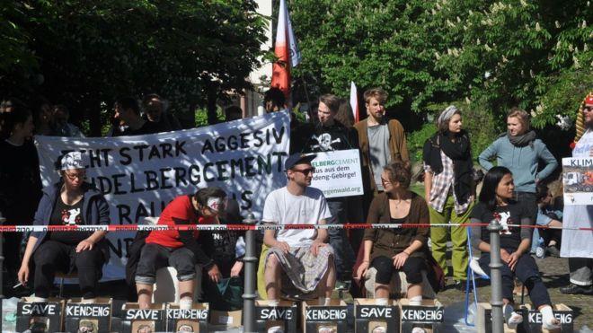 Pengunjuk rasa menyemen kakinya di depan Balai Kota Heidelberg, untuk mendukung para petani Kendeng. (Lampungnews.com/bbc.com