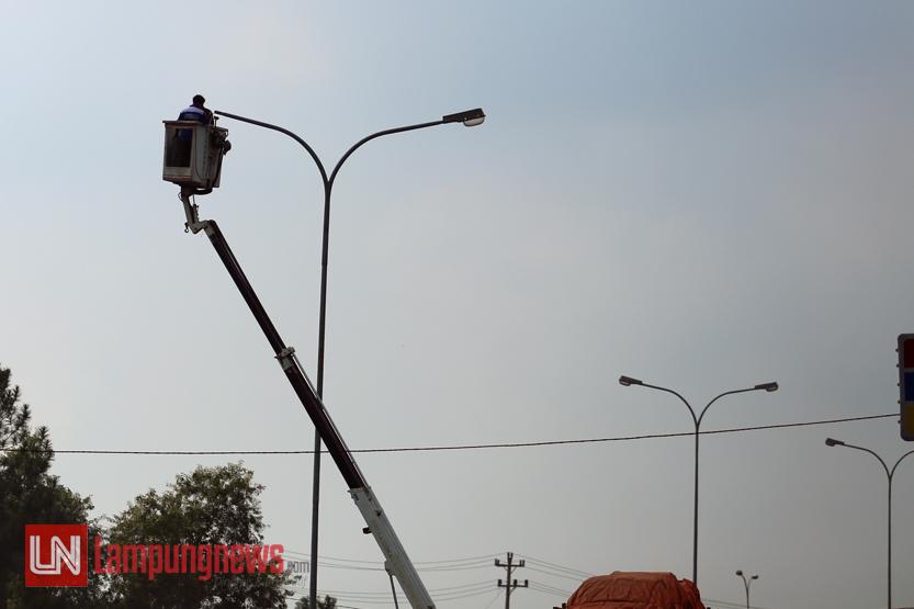 Dua pekerja memeriksa dan memperbaiki lampu-lampu jalan di Jalan Soekarno – Hatta, Rabu (17/5). Pengecekan dan perbaikan ini untuk menyambut Ramadan dan juga arus mudik Lebaran, lantaran Jalan Soekarno – Hatta kerap dikeluhkan gelap dan membahayakan oleh para pemudik. (Lampungnews/El Shinta)