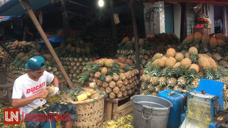 Firman, pedagang nanas di Pasar Pasir Gintung sedang mengupas nanas pesanan konsumen. Firman mengaku banyak konsumen yang memesan untuk membuat kue nastar. (Lampungnews/Dinda)