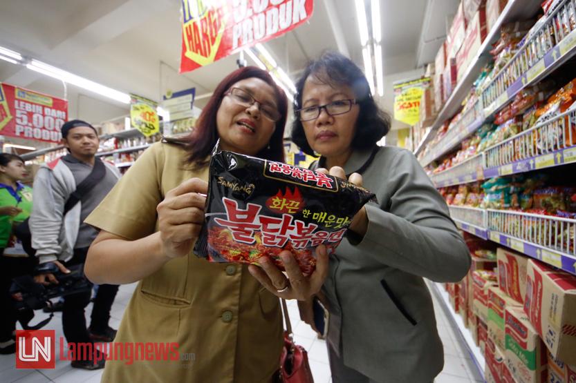 Petugas memeriksa nomor izin mie instan asal Korea Selatan yang belakangan santer terkenal sebagai produk tidak halal di Hypermart, Senin (5/6). (Lampungnews/El Shinta)