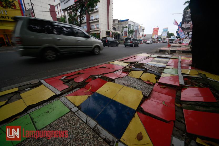Kondisi trotoar di Jalan Raden Intan yang keramiknya mulai terkelupas dan retak, Sabtu (1/7). Kerusakan fasilitas umum ini kerap dikeluhkan bagi pejalan kaki karena dianggap kurang nyaman. (Lampungnews/El Shinta)
