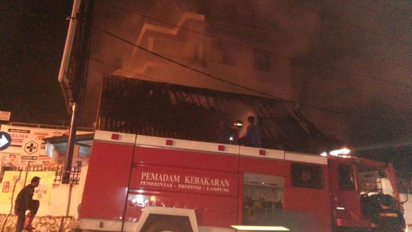 Petugas BPBD memadamkan api yang memberangus Apotik Alifa di Jalan Agus Salim, Kelapa Tiga Permai, Tanjung Karang Pusat, Senin (17/7) sekitar pukul 04.30 WIB. (Foto: BPBD Bandarlampung)