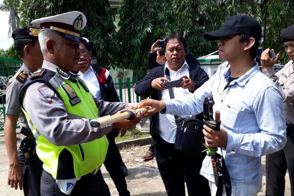 Polisi mengambil senjata yang ditemukan di siring dan balik pohon saat bentrokan terjadi.