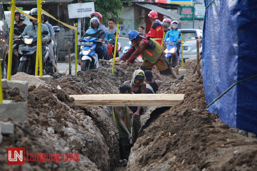 Sejumlah pekerja mengeruk saluran pemasangan pipa gas bumi di Jalan Panglima Polim, Selasa (11/7). Program dari Kementerian ESDM ini direncanakan akan menyentuh 10 ribu KK di Bandarlampung. (Lampungnews/El Shinta)