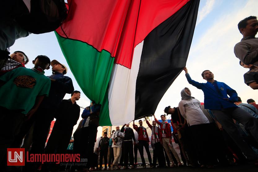 Ratusan massa yang tergabung dalam Aliansi Lampung Membela Masjid Al Aqsa menggelar aksi 27717 untuk menyerukan kutukan terhadap tindakan kejam Israel terhadap warga Palestina dan pelarangan aktivitas di Masjid Al Aqsa, di Tugu Adipura, Kamis (27/7). (Lampungnews/El Shinta)