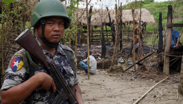 Seorang petugas penjaga perbatasan Myanmar berjaga di depan sisa-sisa sebuah rumah yang terbakar dalam bentrokan antara tersangka militan dan pasukan keamanan di desa Tin May, kota Buthidaung, negara bagian Rakhine utara, Myanmar, 14 Juli 2017. Nasib mencekam muslim Rohingya di Tanah Emas.