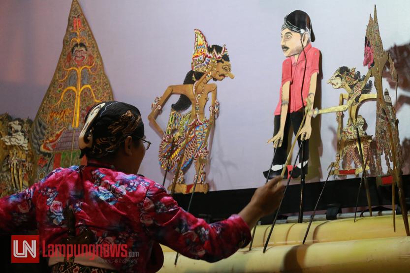 Aksi dalang yang memainkan wayang kulit dengan sinden lagu jawa pada Festival Dalang Wayang Kulit 2017 di Tugu Adipura, Minggu (20/8). Festival yang digelar Pemkot Bandarlampung dalam rangka HUT ke-72 Kemerdekaan Indonesia ini diikuti 128 peserta dari seluruh kabupaten/kota se-Lampung. (Lampungnews/El Shinta)