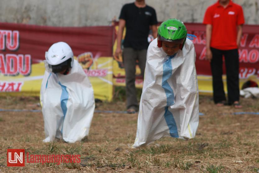 Dua orang bocah saling berkejaran dengan menggunakan pakaian khusus pada perlombaan GP Karung atau balap karung. Uniknya, perlombaan yang dimodifikasi dari balap karung ini mewajibkan peserta menggunakan helm dan masuk ke dalam karung layaknya seorang pembalap. (Lampungnews/El Shinta)