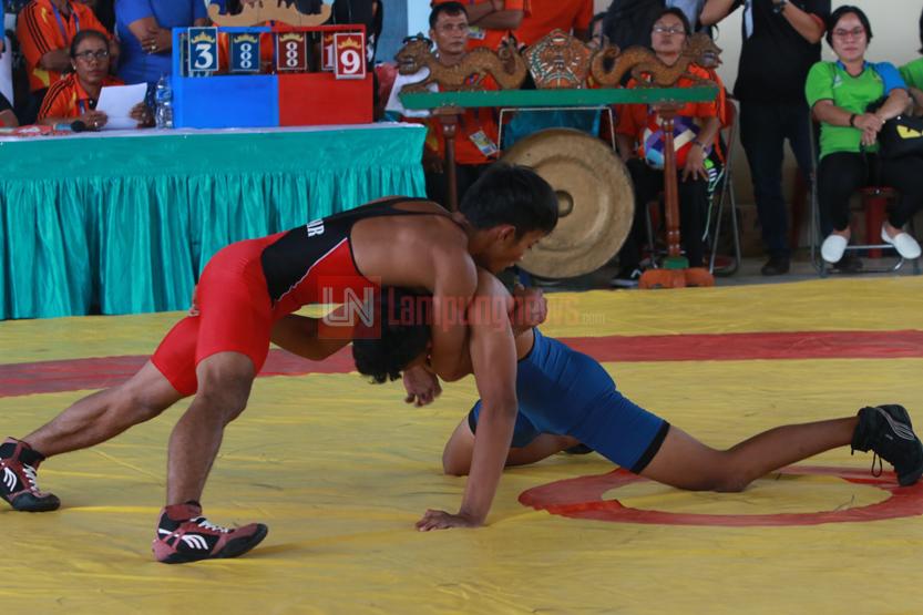 Atlet gulat dari Lampung Barat, Junaidi (merah) melakukan kuncian ke lawannya yakni Delvio A Dandi (biru) dari Bandarlampung pada pertandingan final gulat yang digelar di Hall C pada Porprov ke-VIII Lampung, Senin (28/11). (Lampungnews.com/El Shinta)