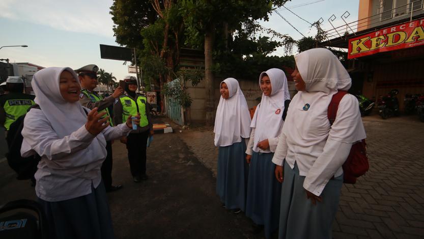 Empat siswi salah satu SMA di Bandarlampung dihukum personel Satlantas Polresta Bandarlampung menyanyikan lagu nasional Garuda Pancasila setelah ditilang lantaran tidak memiliki SIM saat gelaran Operasi Zebra 2017 di Tugu Adipura, Rabu (1/11). (Lampungnews.com/El Shinta)