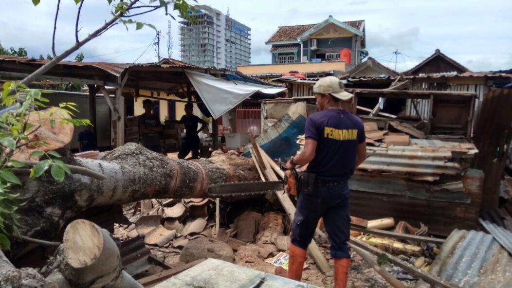 Petugas BPBD menebang pohon tumbang yang menimpa kios di Pasar Buah, Sumur Putri, Telukbetung Selatan, Jumat (1/12). (Lampungnews.com/El Shinta)