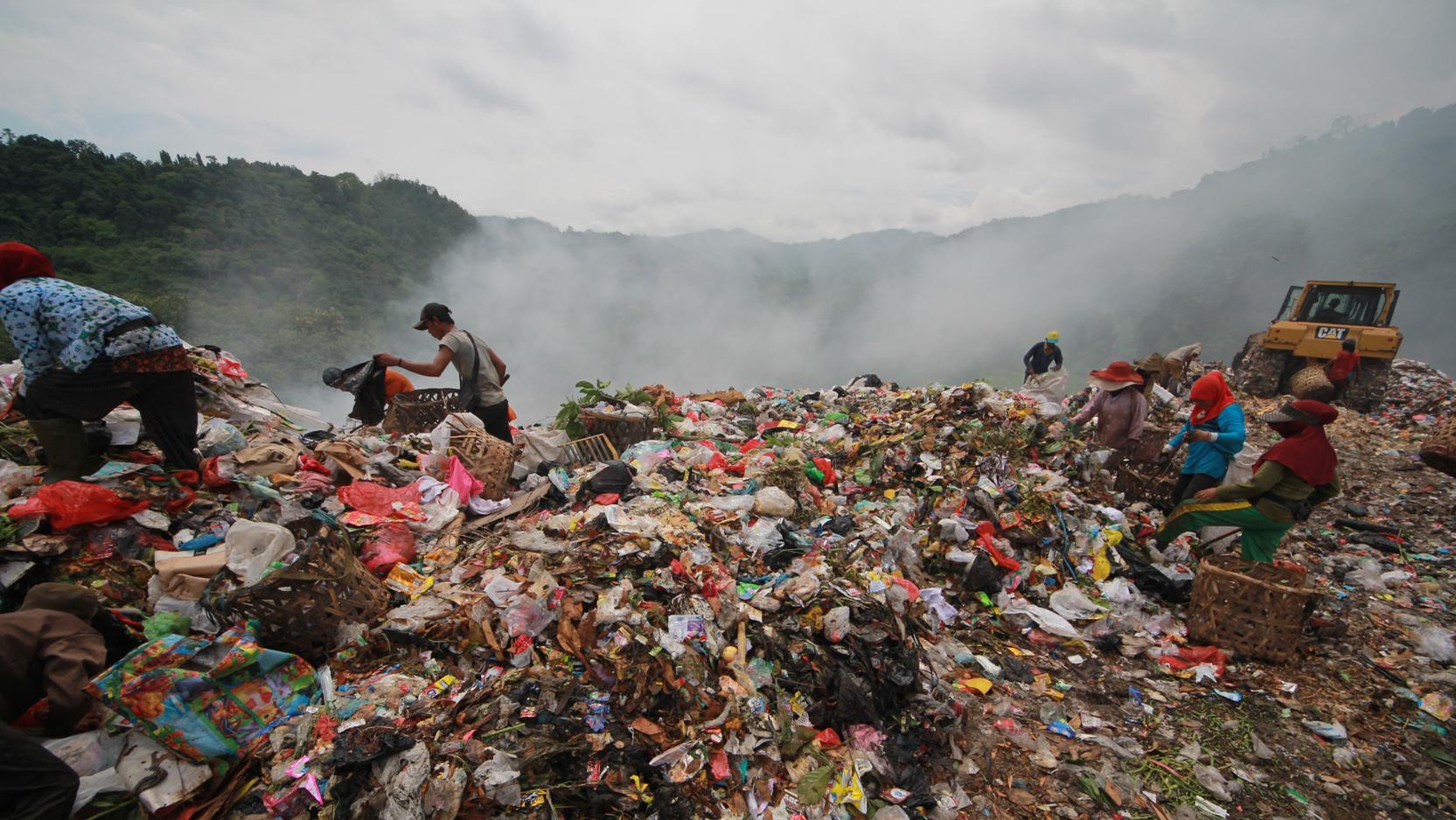 Pemulung mencari barang-barang bekas di antara tumpukan sampah meski asap putih sisa kebakaran kemarin masih mengepul, Jumat (8/12). (Lampungnews.com/El Shinta)