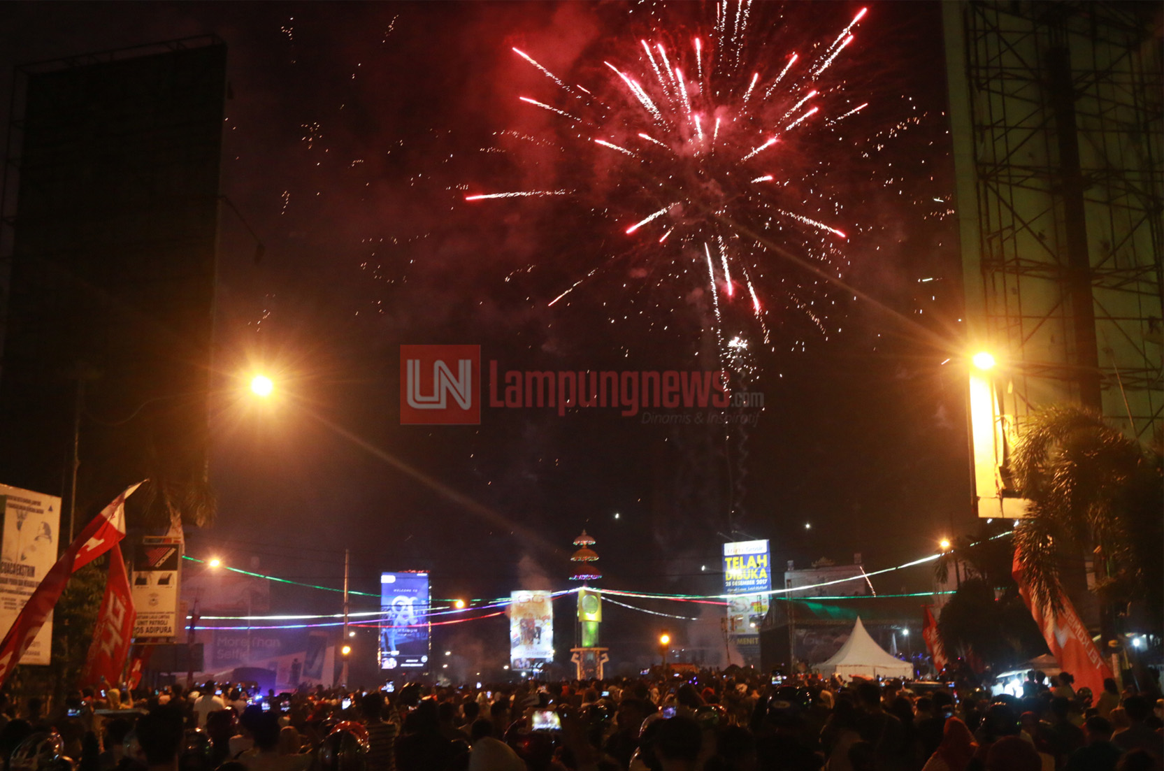 Ribuan warga memadati Tugu Adipura untuk menyaksikan pesta kembang api pada malam pergantian tahun pada 31 Desember 2017 menuju 1 Januari 2018. Momen pesta kembang api ini banyak diabadikan warga melalui kamera ponsel. (Lampungnews.com/El Shinta)