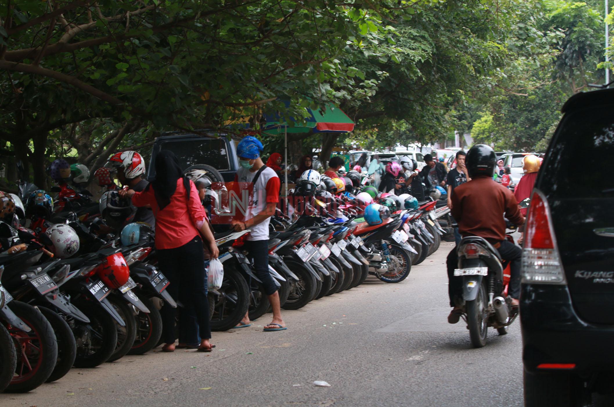 Sejumlah kendaraan roda empat dan roda dua parkir di bahu jalan Sultan Agung, Minggu 7 Januari 2018. Parkir liar di bahu jalan ini sudah ada sejak Transmart Lampung dibuka dan menyebabkan arus lalu lintas menjadi semerawut. (Lampungnews.com/El Shinta)