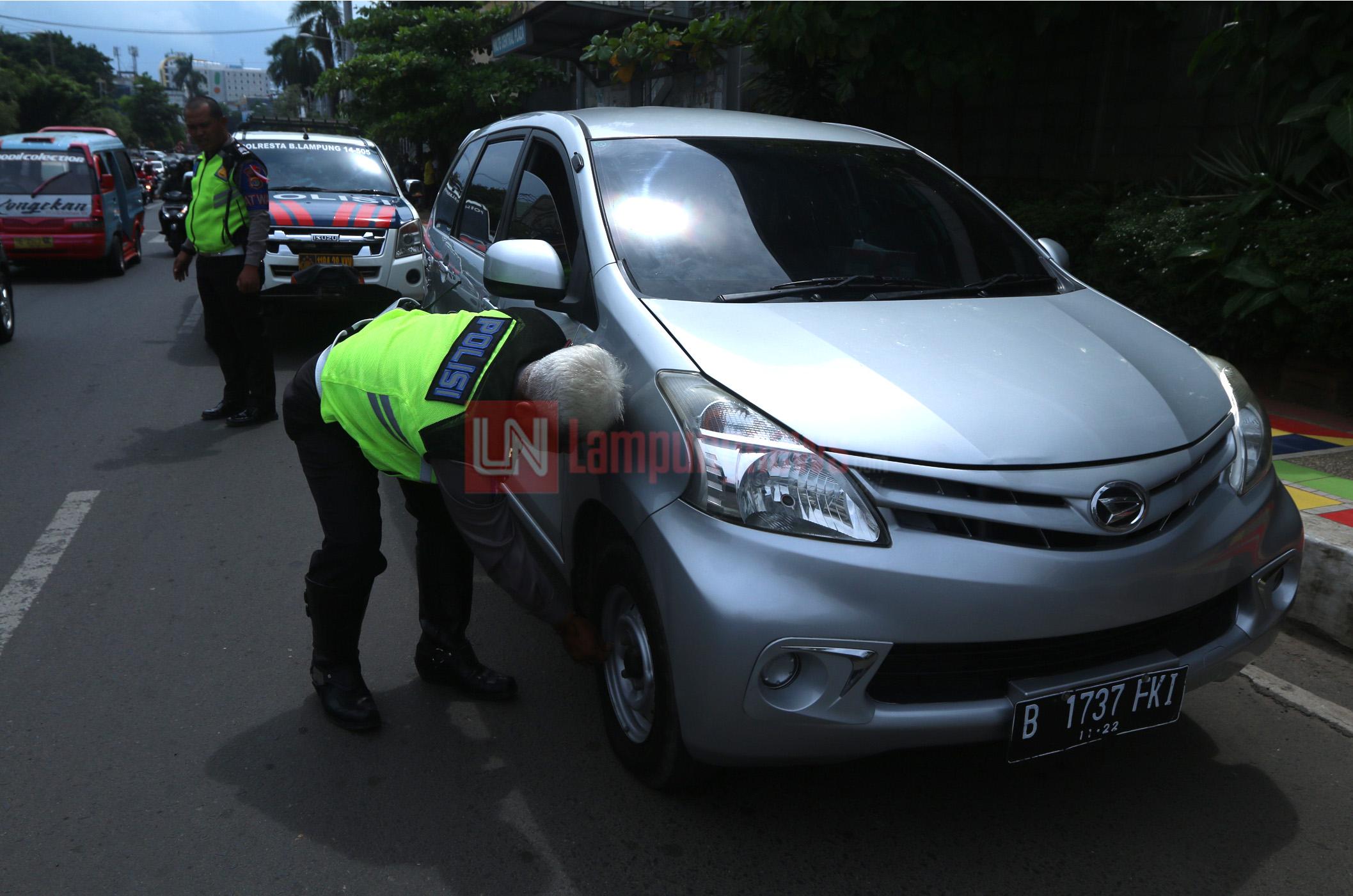 Anggota Satlantas Polresta Bandarlampung menggembosi ban mobil warga yang parkir di badan Jalan Kartini di depan Central Plaza, Kamis (18/1). Cara ini mulai dilakukan sejak awal tahun untuk mobil yang parkir di badan jalan protokol. (Lampungnews.com/El Shinta)