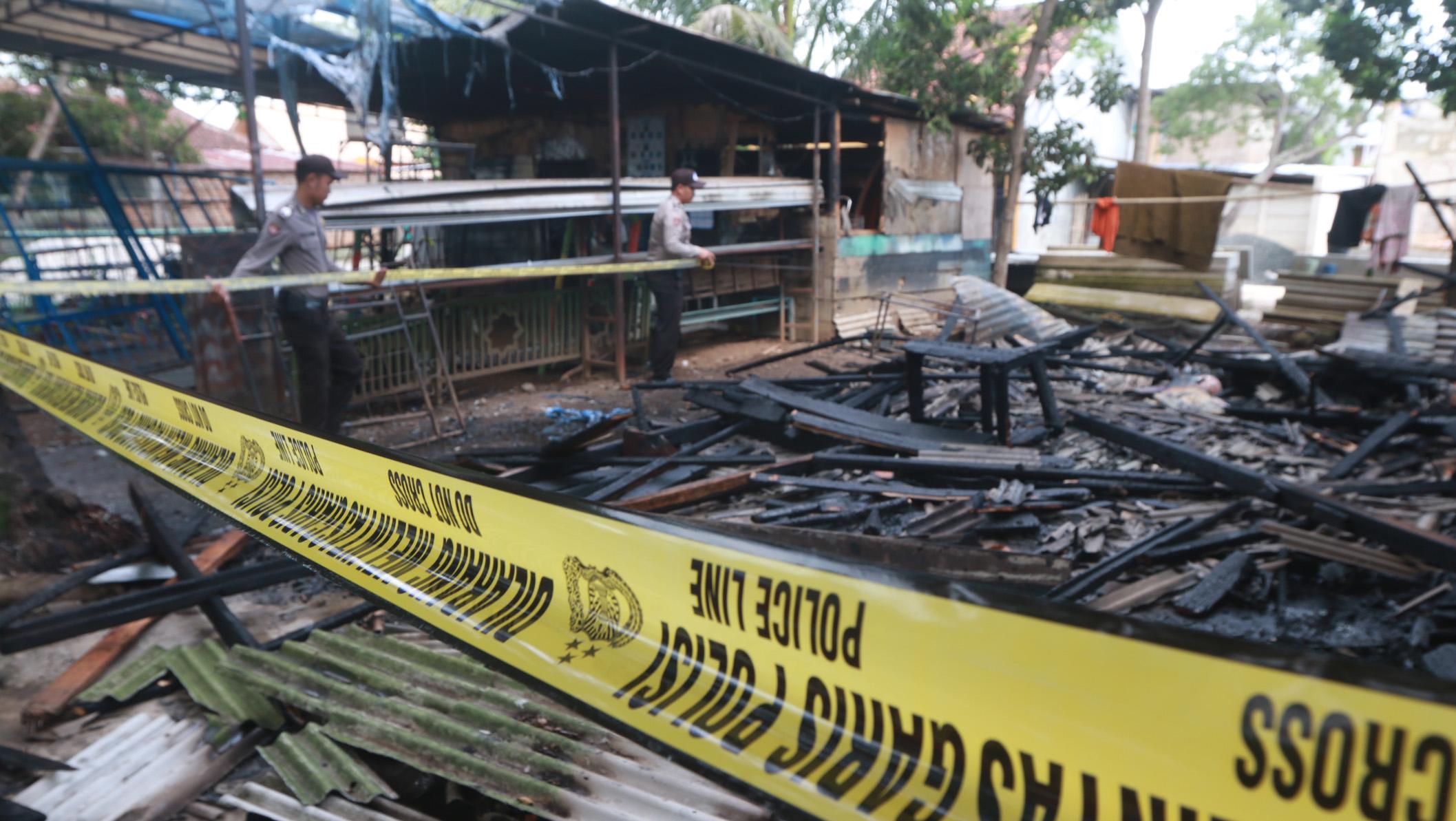 Polisi memasang police line di area kios yang terbakar di Jalan Untung Suropati, Labuhan Ratu, Rabu (10/1). (Lampungnews.com/El Shinta)