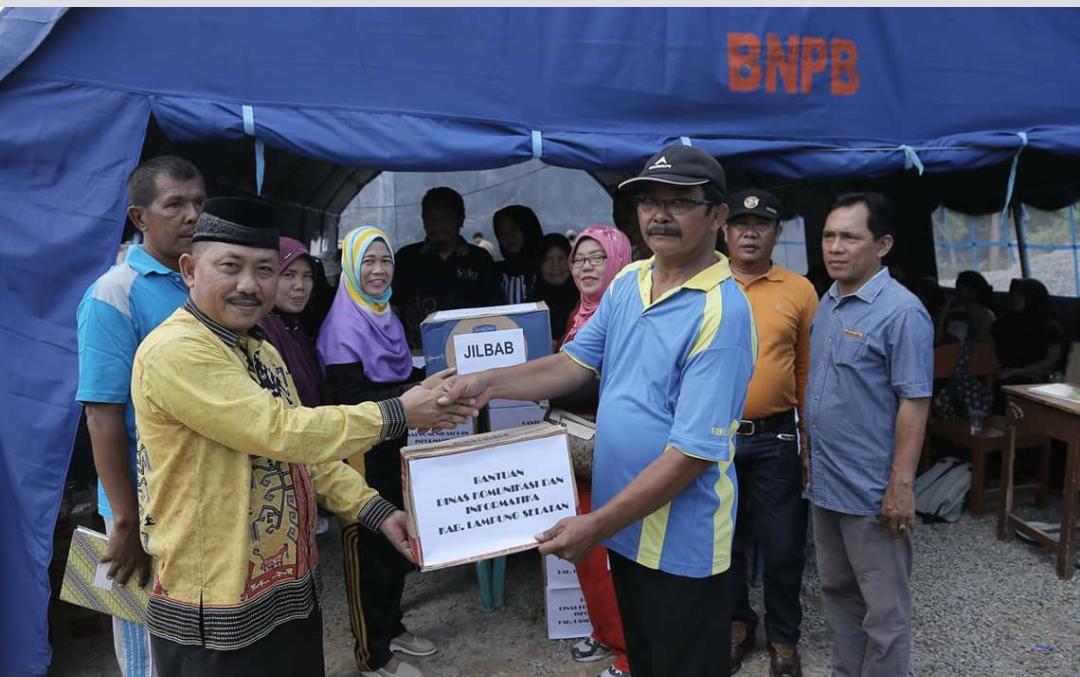 Kadiskominfo Lamsel Hendra Jaya  (kiri) memberikan bantuan kepada perwakilan korban banjir di Kalianda (Diskominfo Ls)