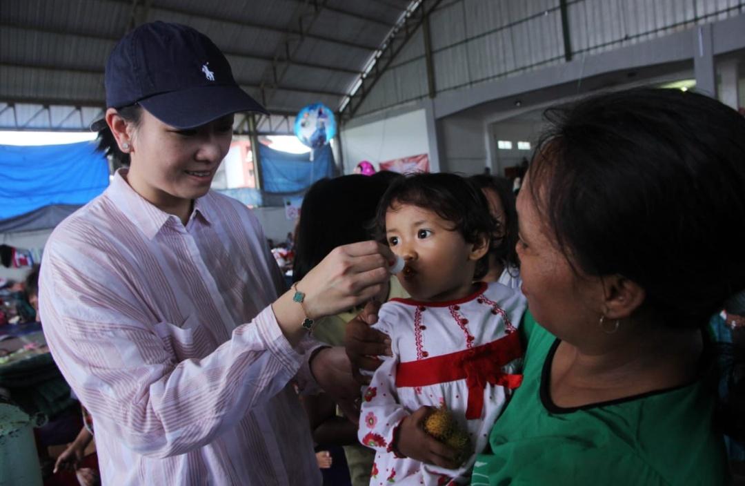 Ny Pitka Rycko Menoza sedang memberikan multivitamin kepada salah satu anak pengungsi di Lapangan Tennis Indoor, Kalianda, (4/1).